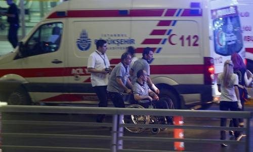 Nhân viên y tế hỗ trợ một người ngồi xe lăn rời khỏi sân bay Ataturk. Ảnh: Reuters.