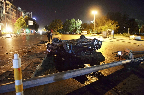A flipped car lies in a road near military headquarters in Ankara, Turkey July 16, 2016. REUTERS/Stringer