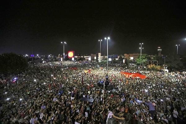 Người dân tập trung phía ngoài sân bay Ataturk, thành phố Istanbul, nơi phi cơ chở Tổng thống Thổ Nhĩ Kỳ hạ cánh xuống. Ảnh: Reuters.