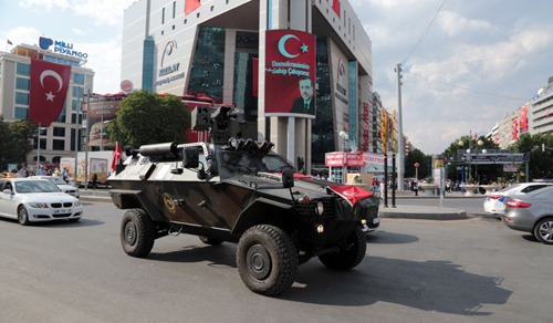 [Caption]A police APC drives in Kizilay Square with a poster of Turkeys President Recep Tayyip Erdogan in the background in Ankara, Turkey, Thursday, July 21, 2016. The stunning sweep of Turkeys crackdown following an attempted coup last week forces questions about how far President Recep Tayyip Erdogan will go to cement his personal power at the expense of accepted democratic ideals. (AP Photo/Burhan Ozbilici)