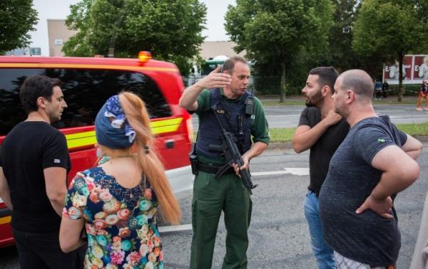 Cảnh sát giải thích thông tin cho người dân gần trung tâm mua sắm Olympia. Ảnh: AFP