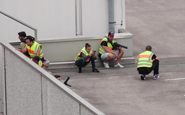 [Caption]A screen grab taken from video footage shows plain clothes police officers taking cover in the car park of the Olympia shopping mall during shooting rampage in Munich, Germany