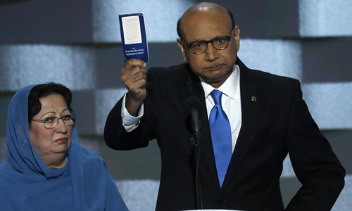 Khizr Khan, whose son, Humayun S. M. Khan was one of 14 American Muslims who died serving in the U.S. Army in the 10 years after the 9/11 attacks, offers to loan his copy of the Constitution to Republican U.S. presidential nominee Donald Trump, as he speaks while a relative looks on during the last night of the Democratic National Convention in Philadelphia, Pennsylvania, U.S. July 28, 2016. REUTERS/Mike Segar