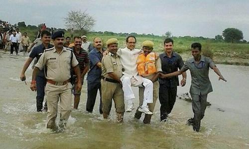 Thủ hiến Shivraj Singh Chouhan bị chế giễu vì để hai cảnh sát khiêng qua chỗ nước ngập. Ảnh: Indian Express.