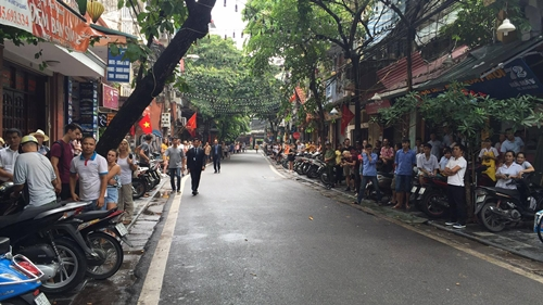 Người dân đứng chờ hai bên một con phố