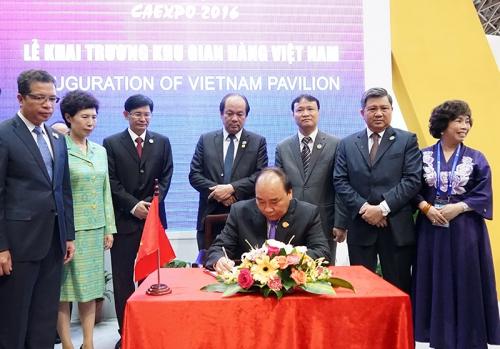 Thủ tướng viết lưu bút tại Khu gian hàng thương mại của DN Việt Nam. Ảnh: VGP