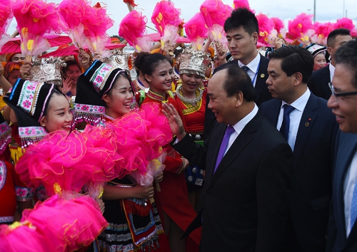 Thủ tướng Nguyễn Xuân Phúc chào các sinh viên Trung Quốc ra đón đoàn tại sân bay. Ảnh: VGP/Quang Hiếu
