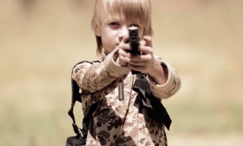 Bé trai tóc vàng chỉ khoảng 10 tuổi xuất hiện trong video tuyên truyền của Nhà nước Hồi giáo. Ảnh: Mirror.