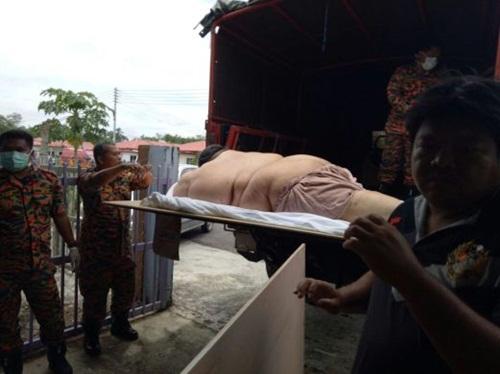 Người đàn ông Malaysia béo phì được đưa lên xe tải đến bệnh viện cấp cứu. Ảnh: NST