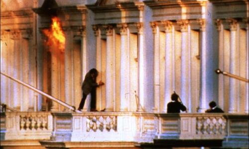 Một con tin cố gắng trèo ra ngoài căn phòng bốc cháy trong cuộc đột kích. Ảnh: History