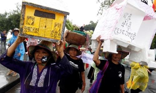 Dân khiếu kiện đất đai ở Campuchia biểu tình với mô hình ngôi nhà trên đầu. Ảnh: Reuters.