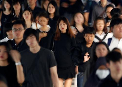 Hành khách mặc đồ đen và trắng, để tang nhà vua mới qua đời, trong giờ cao điểm tại ga tàu ở Bangkok. Ảnh: Reuters
