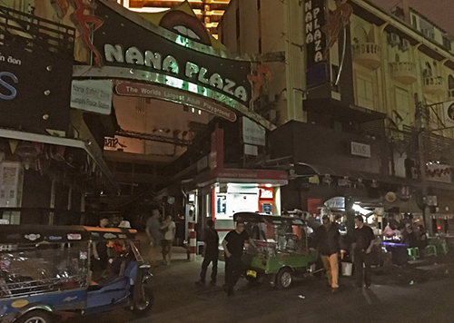 People walk past Bangkoks Nana Plaza red-light district, after it closed down temporarily following the death Thursday of Thailands 88-year-old King Bhumibol Adulyadej
