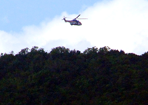 Chiếc trực thăng quần thảo trên đỉnh núi. Ảnh: Phước Tuấn