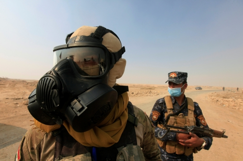 Iraqi forces wear protective masks after winds brought fumes from a nearby sulfur plant set alight by Islamic State militants, at south of Mosul in Qayyara