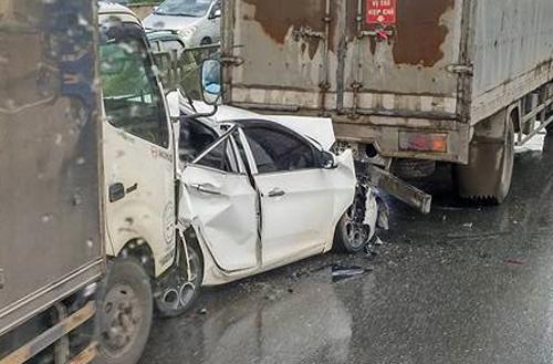 Chiếc Kiamoning bị kẹp ở giữa 2 xe tải và bị biến dạng.Ảnh: Minh Thuận