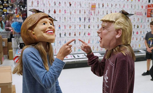 Kids play with masks of presidential candidates Hillary Clinton and Donald Trump inside a costume shop in Washington. Picture: McClatchy Tribune