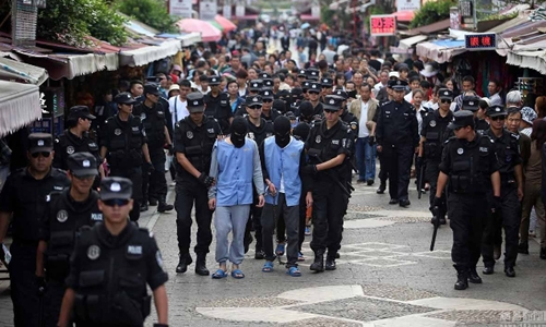 12 tên cướp vị thành niên bị cảnh sát bắt diễu phố hôm 25/10 tại Côn Minh, Vân Nam, Trung Quốc. Ảnh: Shanghaiist.