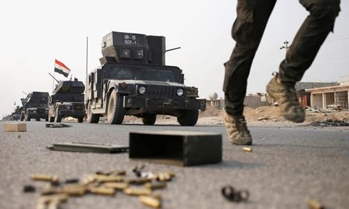 Một binh sĩ Iraq lao về hướng thành phố Mosul với các xe quân sự phía sau. Ảnh: Reuters.