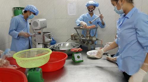 Công nhân đang cho thịt vào máy xay để làm giò sống. Ảnh: công ty Nam Phát