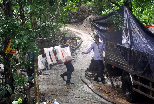 Các lực lượng dân quân địa phương vận chuyển các mảnh vỡ xuống núi phục vụ công tác điều tra. Ảnh: Thái Hà