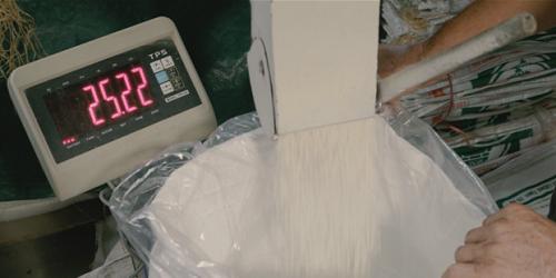 Gạo đang được cân và đóng gói trong quy trình khép kín. Ảnh: bizmedia