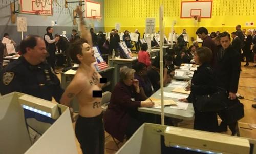 Một phụ nữ ngực trần bị cảnh sát bắt ở nơi Donald Trump bỏ phiếu. Ảnh: New York Daily News.