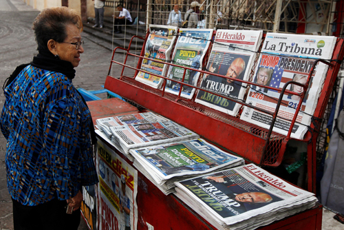 A woman looks at newspapers with cover stories about the victory of U.S. Republican president-elect Donald Trump, at a newspaper stand in Tegucigalpa, Honduras, November 9, 2016. REUTERS/Jorge Cabrera