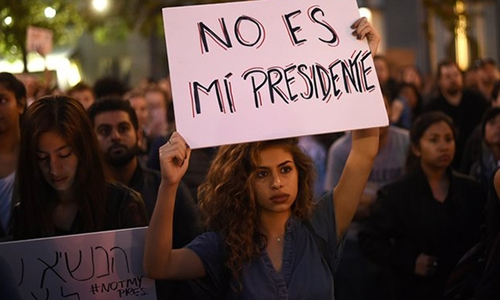 Người biểu tình giơ biểu ngữ Ông ta không phải tổng thống của tôi. Ảnh: Reuters