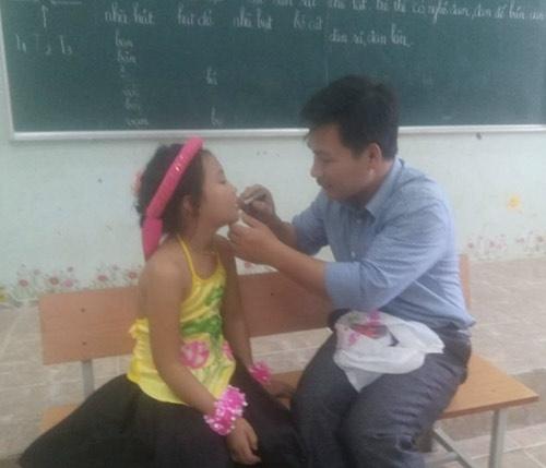 Thầy Cương cẩn thận đánh son cho học sinh.