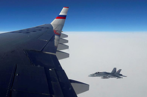 [Caption]A view from an Ilyushin Il-96 plane, transporting journalists and officials of the Russian delegation heading for the Asia-Pacific Economic Cooperation (APEC) summit, shows a Swiss Air Force F/A-18 fighter jet in the airspace above Switzerland, November 18, 2016. REUTERS/Denis Pinchuk/File Photo
