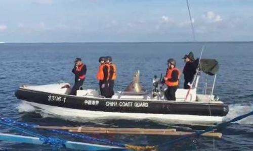 Tuần duyên Trung Quốc đi trên xuồng cao tốc, chĩa súng xua đuổi ngư dân Philippines ở bãi cạn Scarborough. Ảnh: ABS-CBN.