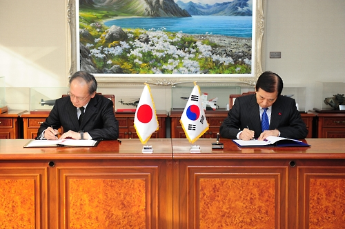 South Koreas Defense Minister Han Min-koo (R) and Japanese Ambassador to Seoul Yasumasa Nagamine sign the General Security of Military Information Agreement (GSOMIA) at the defense ministry in Seoul. (Yonhap)