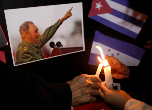 People place candles beside a picture of Fidel, as part of a tribute, following the announcement of the death of Cuban revolutionary leader Fidel Castro, in Tegucigalpa, Honduras November 26, 2016. REUTERS/Jorge Cabrera