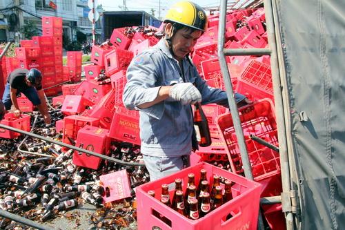 Một người dân đi đường phụ giúp tài xế phân loại bia sau vụ tai nạn. Ảnh: Phước Tuấn