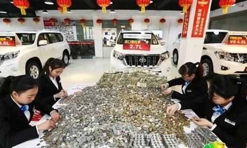 Các nhân viên đại lý ôtô phải đếm đống tiền xu suốt 12 giờ. Ảnh: SCMP.