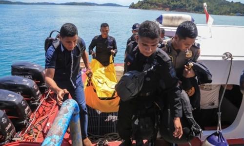 Cảnh sát Indonesia mang túi đựng xác và mảnh vụn máy bay lên bờ. Ảnh: AFP.