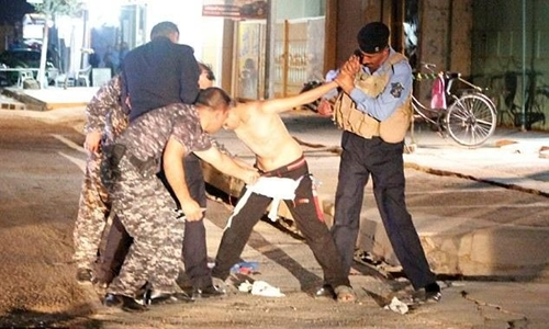 Iraqi security forces wrestle with a young would-be suicide bomber in the city of Kirkuk CREDIT: REUTERS