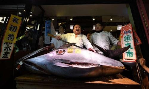 Kiyoshi Kimura và con cá ngừ vây xanh mua được với giá hơn 630.000 USD. Ảnh: AFP