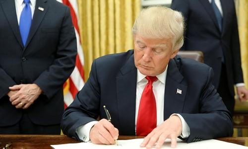 Tổng thống Donald Trump ký những sắc lệnh đầu tiên khi ngồi vào phòng Bầu dục, Nhà Trắng. Ảnh: Reuters
