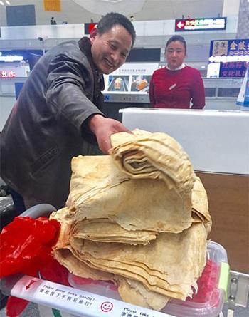 nguoi-dan-ong-mang-15-kg-banh-trang-me-lam-len-may-bay