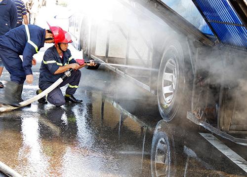 Lính cứu hoả phun nước, dập ngọn lửa. Ảnh: Quảng Lâm
