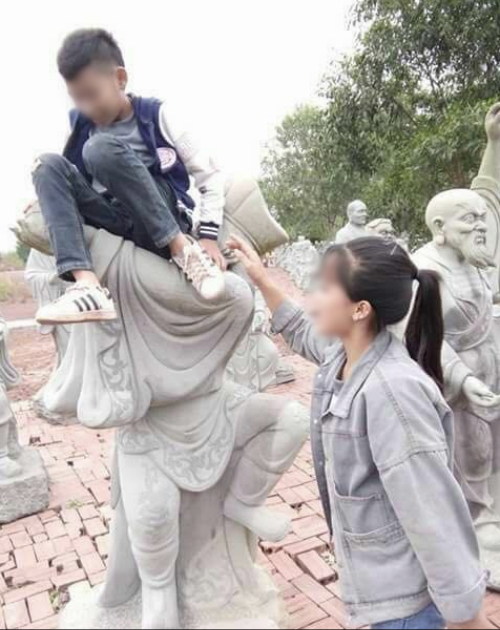 hai-co-gai-ngoi-len-tuong-phat-chup-anh-gay-phan-no-1