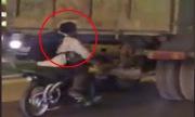 Thanh niên chạy xe máy núp sau đuôi ôtô tải