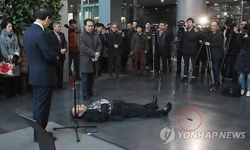 Ông lão 79 gục xuống sàn sau khi tự đâm vào mình trước mặt thị trưởng Seoul. Ảnh: Yonhap