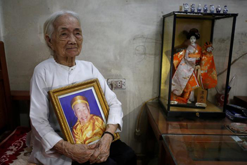 Vietnamese Nguyen Thi Xuan, 94, who married Japanese soldier Nguyen Van Duc during World War Two, poses with a portrait of him at her house in Hanoi, Vietnam February 22, 2017. REUTERS/Kham