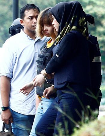 Đoàn Thị Hương được mặc thêm áo chống đạn bên ngoài chiếc áo ban đầu và còng tay vào một nữ cảnh sát Malaysia,