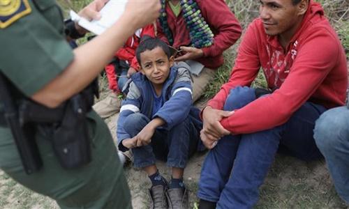 Lực lượng tuần tra biên giới Mỹ xem xét giấy khai sinh của trẻ em ở Texas. Ảnh: AFP