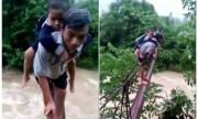 Người lớn cõng trẻ đi học trên ống dẫn nước vượt suối chảy xiết