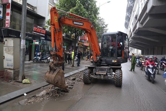Máy xúc xuống đường dọn dẹp vỉa hè ở Hà Nội